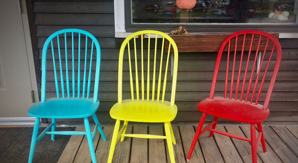 3 brightly colored wooden chairs on a porch