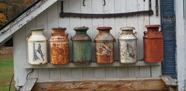 old metal jugs lined up outside a white barn